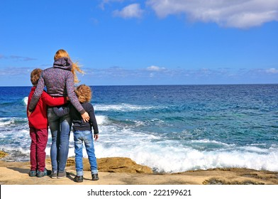 Mum with kids standing at the Mediterranean sea, Malta