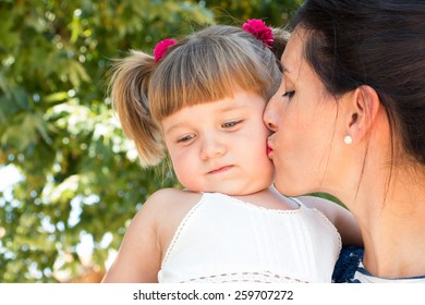 Mum kissing her angry little daughter