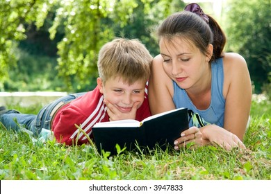 Mum and the son reads the book on a lawn in park