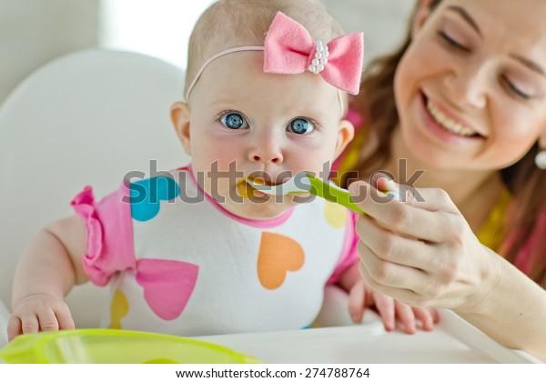 Mum spoon-feeds the child