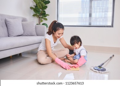 mum teaching daughter cleaning their home living room at weekend. A young woman and a little child girl dusting. family housework and household concept.