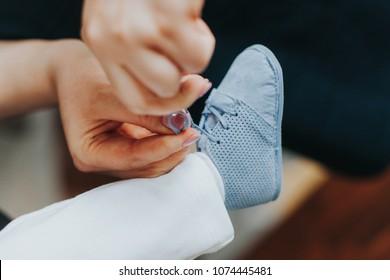 Mum tying baby boy's blue shoes