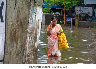 Mumbai / India 01 July 2019 A Indian woman wades through a waterlogged street during monsoon rain talking on her mobile phone at Mumbai Maharashtra India
