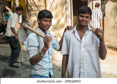 MUMBAI, INDIA - 08 JANUARY 2015: Two young Indian workers stand in street with hoe's in hands. Young boys and girls work as cheap labor throughout India.