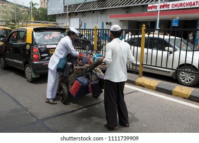 Mumbai / India 08 June 2018 Dabbawala carrying lunch boxes for delivery in the city in Mumbai Maharashtra India
