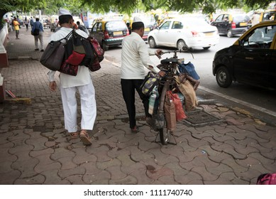 Mumbai / India 08 June 2018 Tiffinwala or dabbawala carrying lunchboxes on bicycle  in Mumbai Maharashtra India