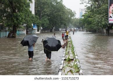 Mumbai / India 09 July 2018 People wading through flooded street during heavy rains in Mumbai Maharashtra India
