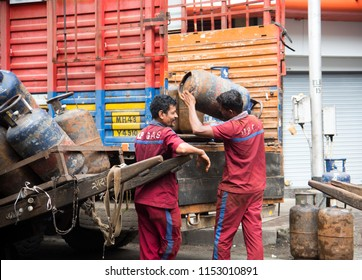 MUMBAI, INDIA, 1 AUGUST 2018 : Indian worker delivering LPG gas cylinders to customers on busy street of Mumbai.