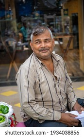 Mumbai, India, 10 january 2020. Street photography in lively market. Portrait of a vegetable seller sitting on the floor, looking shyly away and smiling.