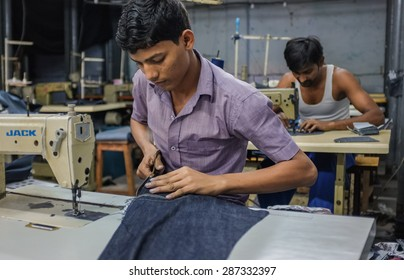 MUMBAI, INDIA - 12 JANUARY 2015: Indian workers sewing in a clothing factory in Dharavi slum