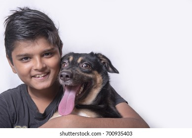 Mumbai / India 13 August 2014 Close-up of a happy young boy with his indian breeds pet  Dog in front of white background  at Mumbai Maharashtra India