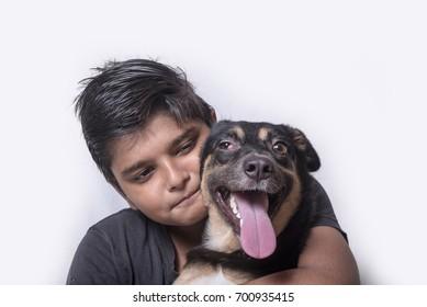 Mumbai / India 13 August 2014 Young Boy Hugging His indian  breeds Dog in front of white background at Mumbai Maharashtra India