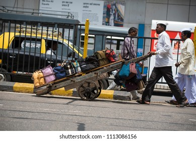 Mumbai / India 14 June 2018 Tiffinwala or dabbawala carrying lunchboxes in crate on handcart at Churchgate railway station in Mumbai Maharashtra India