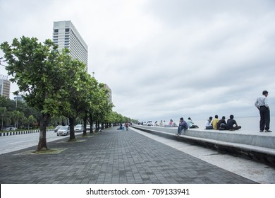 MUMBAI, INDIA 17 SEPTEMBER 2016 : Unidentified people walk on Marine Drive  Marine Drive is a 3-kilometre-long boulevard in South Mumbai, It is a road along the coast.