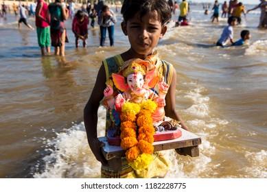 Mumbai / India 17 September 2018 Boy carry a statue of the Hindu god Ganesh the deity of prosperity to be immersed into the Arabian Sea on the fifth day at Juhu beach Mumbai India