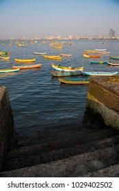 Mumbai / India 18 February 2018 A stone staircase in the Worli village sea beach and Fishing boat in Bombay Mumbai Maharashtra  India