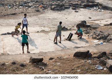 Mumbai / India 18 February 2018 Rural Indian boys playing cricket in the street at Worli village in Bombay Mumbai Maharashtra  India