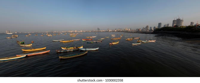 Mumbai / India 18 February 2018 Panoramic view of  Fishing boats in Arabian sea and Mumbai Skyline at sunset from Worli village in Bombay Mumbai Maharashtra  India