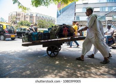Mumbai / India 20 April 2018 Dabbawalla pushing a cart loaded with tiffin boxes through a street At Churchgate Railway in Mumbai  Maharashtra