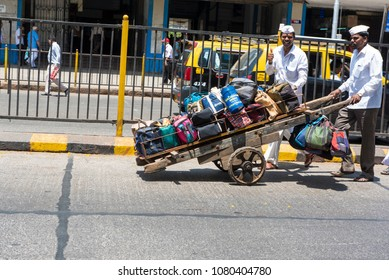 Mumbai / India 20 April 2018 Dabbawalla pushing a cart loaded with tiffin boxes through a street At Churchgate Railway in Mumbai  Maharashtra