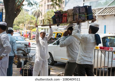Mumbai / India 20 April 2018 Dabbawala carrying lunchboxes on head and talking on mobile at work of providing lunch boxes At Churchgate Railway in Mumbai  Maharashtra