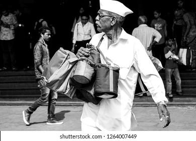 Mumbai, India, 20 november 2018 /  The famous Dabbawala lunchbox service in Churchgate Railway Station; operators in white with white hat carrying full and warm lunchboxes to distribute to their owner