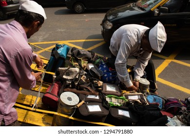 Mumbai, India, 20 november 2018 /  The famous Dabbawala lunchbox service in Churchgate Railway Station; operators dressed in white with white hat carrying full and warm lunchboxes