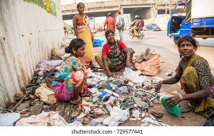 Mumbai, India - 2/1/2011: Indian women sorting garbage on a sidewalk in the slum area