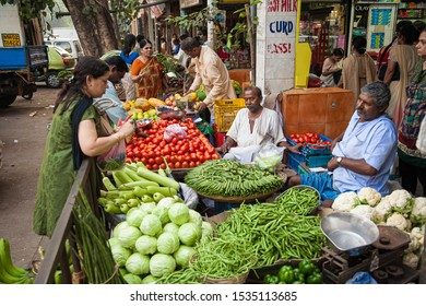 Mumbai, India - 2/2/2011:  Local Indian men and womens shopping for fruit and vegetables at a street market in Mumbai