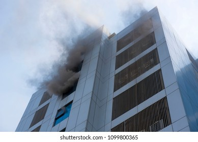 Mumbai / India 27 May 2018 A dark grey smoke billowing out of the Commercial Building from windows after fire at Malad west  Mumbai Maharashtra India
