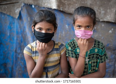 Mumbai / India 29 April 2020 Portrait of urban slum girls wearing face mask to protect against Corona virus spread at Dharavi in Mumbai Maharashtra India