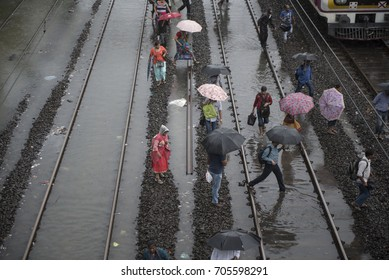 Mumbai / India 29 August 2017 People walk through flooded railway tracks after heavy rains at Dadar railway station in Mumbai Maharashtra  India