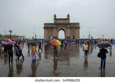 Mumbai / India 30 June 2019 Crowd of people with umbrellas enjoy at The Gateway of India during  rainy season in Mumbai Maharashtra India