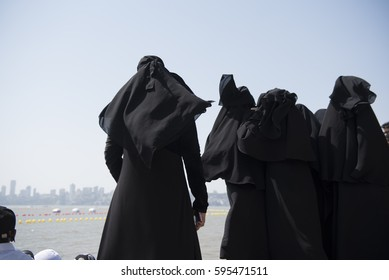 Mumbai / India 5 March 2017  Muslim women wearing black  burkas standing together along the famous  Marine Drive Near Beach at  Mumbai , Maharashtra, India