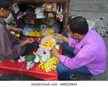 Mumbai, India - April 13, 2016 : Male street vendors making marigolds flower garlands for Hindu gods praying near Colaba market temple