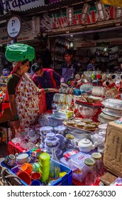 Mumbai, India, April 9 2019. Indian woman carrying heavy green bag in his head and looking for  kitchen accessories on tle local market