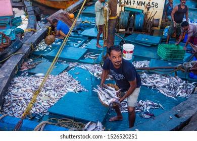 MUMBAI , INDIA - AUG 26 : Indian fishermen working in Sassoon Docks in Mumbai India on August 26 2019 Sassoon Docks is the largest fish market in Mumbai
