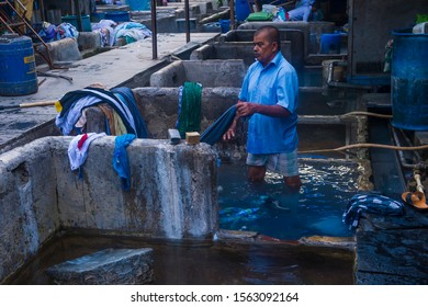 MUMBAI , INDIA - AUG 26 : Indian man work at Dhobi Ghat in Mumbai India on August 26 2019 Dhobi Ghat is an open air laundry in Mumbai over 7,000 people work there daily.