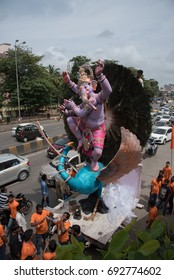 Mumbai, India - August 20, 2016 : Devotees bringing Loard Ganesha from workshop for procession with large crowds during Hindu Lord Ganesha chaturathi festival along the street