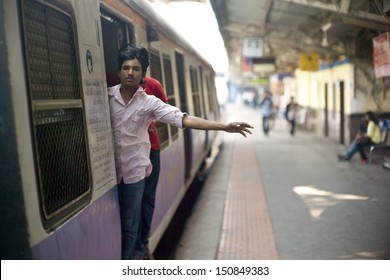 MUMBAI, INDIA - AUGUST 21: Unidentified locals hang themselves outside the train on August 21, 2012 in Mumbai, India. Mumbai Suburban Railway carries more than 7 million commuters on a daily basis.