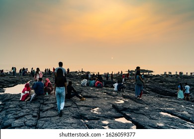 mumbai, India - circa 2020 : People on the bandstand rocky beach enjoying the sunset. This famed landmark is a popular tourist and local spot for sunset views and people wanting to spend quality time