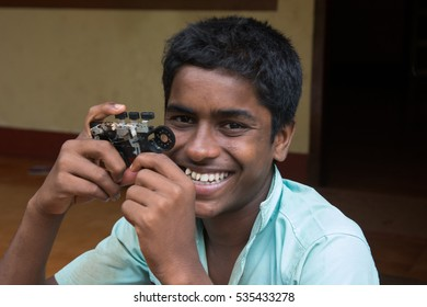 Mumbai, India - December 11, 2016 - Boy from children's home in front of new facility powered by charity from europe with self made camera