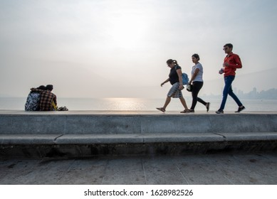 Mumbai, India - December 15, 2017: Lovers on Marine Drive with three passersby, taken at the end of the afternoon