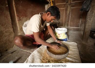 MUMBAI, INDIA - DECEMBER 16, 2018: Unidentified worker removes chaff from grain near Dhobi Ghat in Mumbai