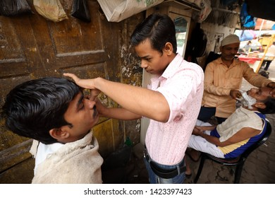 MUMBAI, INDIA - DECEMBER 16, 2018: Unidentified barber shaves a client in the streets near Dhobi Ghat in Mumbai