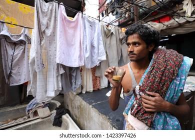 MUMBAI, INDIA - DECEMBER 16, 2018: Unidentified worker drinks tea in the public Dhobi Ghat in Mumbai