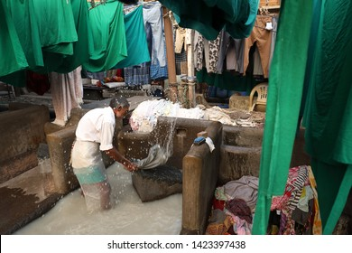 MUMBAI, INDIA - DECEMBER 16, 2018: Unidentified worker does the laundry in the public Dhobi Ghat in Mumbai