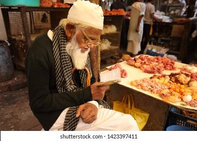 MUMBAI, INDIA - DECEMBER 17, 2018: Unidentified muslim prayer in a market in Chor Bazaar, Central Mumbai