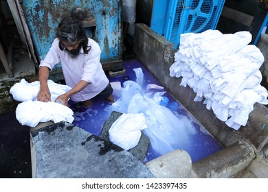 MUMBAI, INDIA - DECEMBER 19, 2018: Unidentified worker does the laundry in the public Dhobi Ghat in Mumbai