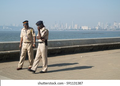 MUMBAI, INDIA - DECEMBER 24, 2016: two police officers are walking along the marine drive near Chowpatty beach